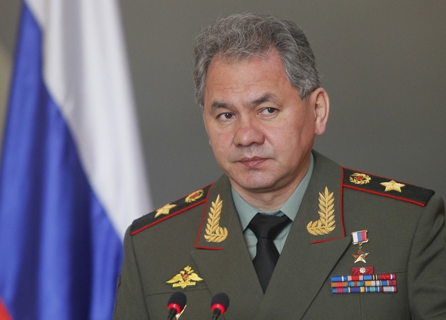 Russia's Defence Minister Sergei Shoigu speaks in front of the Russian flag while attending a news conference after a meeting with his Vietnamese counterpart Phung Quang Thanh in Hanoi on 5 March 2013. (Reuters)