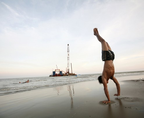 A boy somersaults on a beach outside Pyar Pon Township