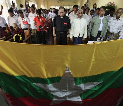 People stand behind Myanmar's national flag during a prayer ceremony for peace between the country's four major religions in Yangon