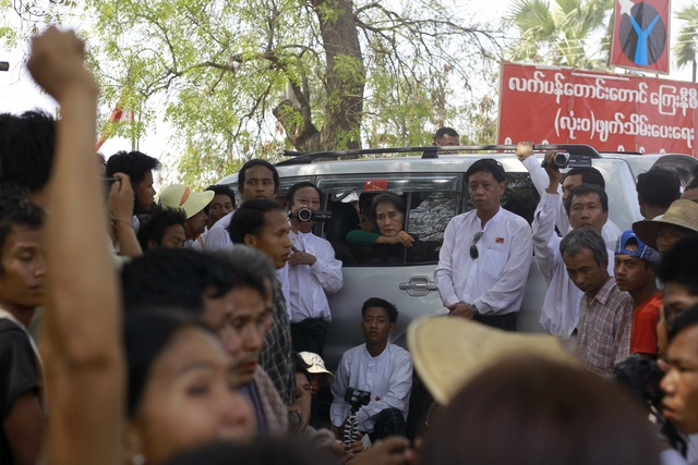 Aung San Suu Kyi watches as villagers protest against an investigation commission's report on a copper mine project on 14 March 2013. (Reuters)