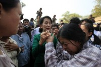 Aung San Suu Kyi comforts a woman at a village in Sarlingyi township on 14 March 2013. (Reuters)