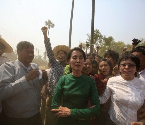 Myanmar pro-democracy Leader Aung San Suu Kyi poses for a photo as villagers protest against an investigation commission's report on a copper mine project in Sarlingyi township