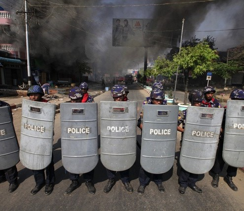 Riot policemen form up near a fire during riots in Meikhtila