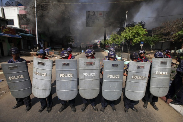 Riot policemen position themselves near a fire during riots in Meikhtila on 22 March 2013. (Reuters)