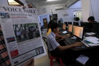 A journalist holds up a sample copy of The Voice Daily newspaper at a newsroom in Rangoon on 31 March 2013. (Reuters)