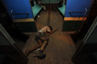 A disabled man sleeps on the floor of a train carriage in Rangoon. (Reuters)