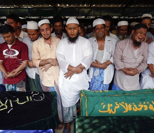 Muslims cry and pray during a funeral for victims of a fire at Yaeway cemetery in Yangon