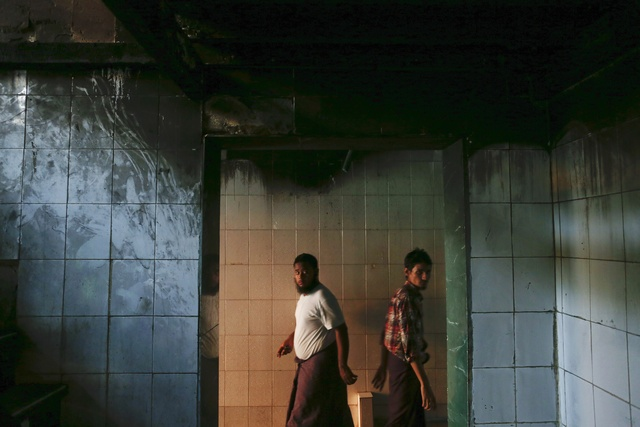 Muslims walk through the Islamic school where 13 boys were killed by a fire in the central, multi-ethnic Botataung district of the former capital Rangoon on 3 April 2013. (Reuters)