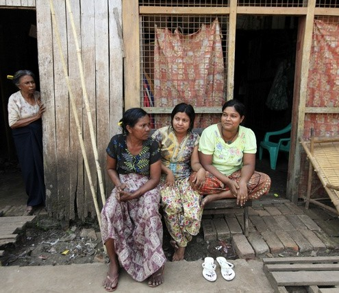 Muslim women sit in front of their home in Letpadan