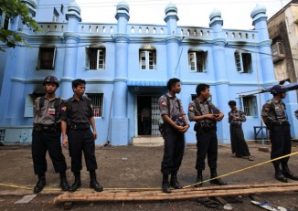 Police stand in front of a mosque and school dormitory that were damaged in a fire in Rangoon on 2 April 2013. (Reuters)