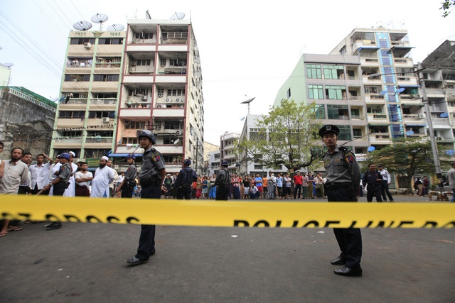 Police stand near a mosque and school dormitory that were damaged by a fire in Yangon