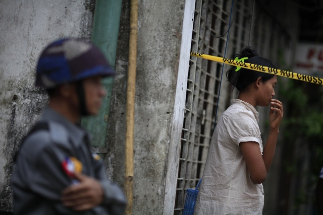 A woman stands behind a police line near a mosque and school dormitory that were damaged by a fire in Yangon