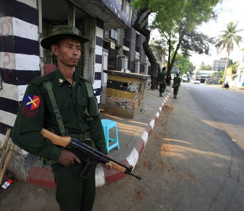 Soldiers stand guard on the side of a street in Meikhtila