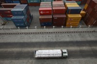 A truck passes near a container yard at a port in Rangoon on 18 April 2013. The EU is expected to lift all sanctions on Burma this week, except for an arms embargo. (Reuters)