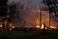 A man looks at buildings on fire during riots at Oakkan village, north of Rangoon on 1 May 2013 (Reuters)
