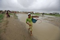 A Rohingya woman carrying her belongings as she moves to a safe place before Cyclone Mahasen was expected to land at an IDP camp near Sittwe, May 2013. (PHOTO: Reuters)