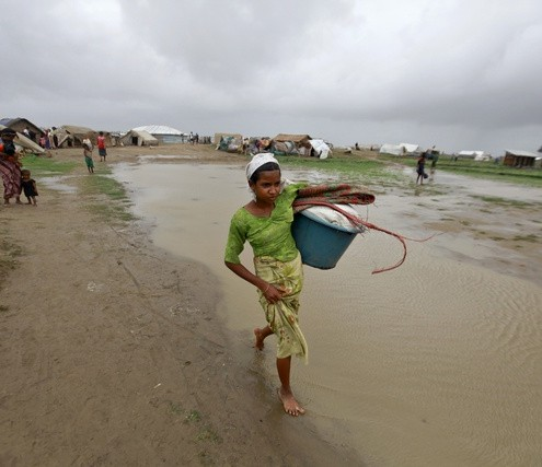 A woman carries her belongings as she moves to safe place before Cyclone Mahasen land at a Rohingya IDP camp outside of Sittwe
