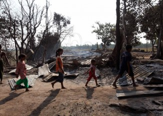 Children walk through debris in Oakkan township, Rangoon Division, which was hit by religious riots on 30 April 2013 (DVB)