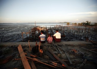 People sit amongst ruins of a burnt neighborhood at East Pikesake ward in Kyaukphyu