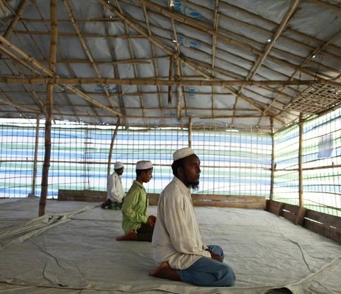 Men offer Friday prayers in a temporary mosque after returning to a Rohingya internally displaced persons (IDP) camp from a shelter from cyclone Mahasen, outside of Sittwe
