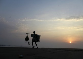 A man from a Rohingya internally displaced persons (IDP) camp carries a fishing net as he walks towards a beach to fish near his camp, outside of Sittwe