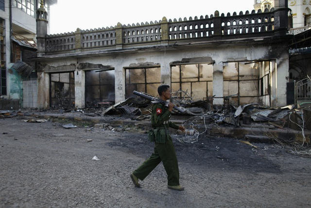 A soldier patrols in front of a mosque that was burnt during a riot between Muslims and Buddhist in Lashio township on 29 May 2013. (Reuters)