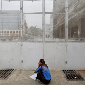 A woman speaks on the phone while reading newspapers outside a construction site in Yangon