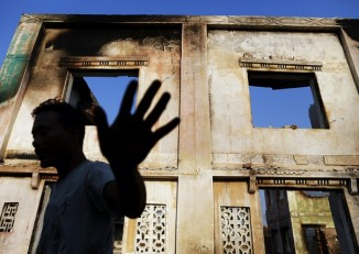 A man reacts toward the photographer as he collects bricks from burnt Muslim homes in Meikhtila