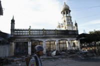 A police officer stands near a mosque, which was burnt during a riot between Buddhist and Muslims in Lashio, Shan state on 29 May 2013. (Reuters)