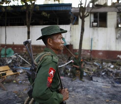 A soldier stands guard in front of mosque that was burnt during riot between Muslims and Buddhist in Lashio township