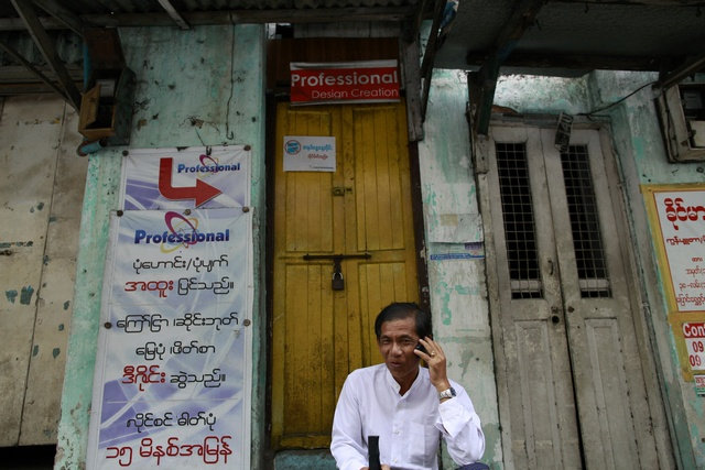 A man talks on his mobile phone by the street side of Rangoon (Reuters)