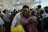 A woman hugs her son who returned from Malaysia at Rangoon International Airport, 15 June 2013 (Reuters)