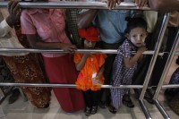 Children wait at Rangoon International Airport for their relatives to return from Malaysia. (Reuters)