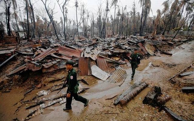 In this file photo from 2012, police officers inspect the aftermath of communal rioting in Arakan State (Photo: Reuters)