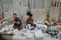 People sort and sell newspapers in central Rangoon on 3 April 2013. (Reuters)