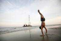A boy does a handstand on a beach outside Pyar Pon Township where ships involved in the construction of a Yadana underwater gas pipeline project are anchored in the background. (Reuters)
