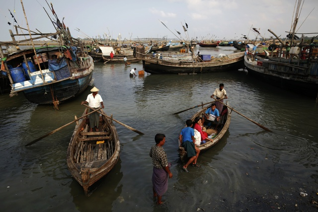 Rohingya people work on their boats near one of many camps for displaced Rohingya on Sittwe's outskirts