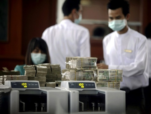 Cashiers seen counting money in a bank in Rangoon. (PHOTO: REUTERS)