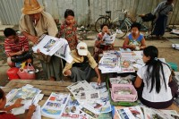 People buy and sell newspapers in central Rangoon on 3 April 2013. (PHOTO: Reuters)