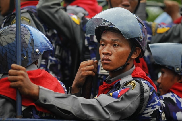 Policemen arrive in their vehicle during the rioting in Sittwe on 10 June 2012. (Reuters)