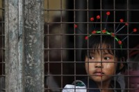 A girl looks from inside a school as she waits for her parents to pick her up in the old part of Rangoon (Reuters)