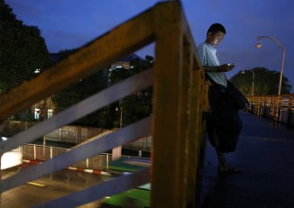 A man use his mobile phone on a bridge in central Rangoon (Reuters)