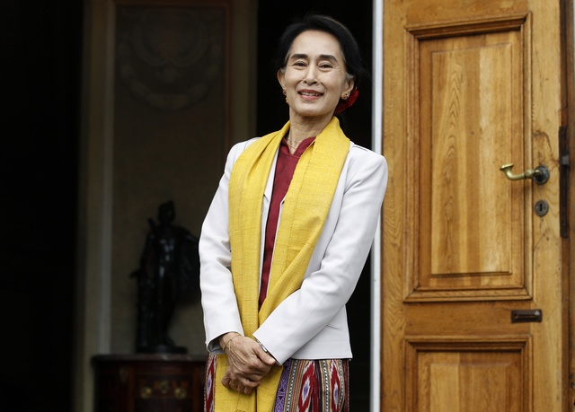 Opposition leader Suu Kyi smiles after her meeting with former Polish president Walesa in Warsaw (Reuters)