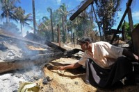 A Muslim man inspects the burnt area of a vandalised mosque in Thabyuchaing village in Sandoway (AFP)