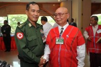 General Mutu Say Poe (R) of the KNU shakes hands with Burmese government official Colonel Tin Win (L) during a break in peace talks in Rangoon in April 2012  (PHOTO: AFP)