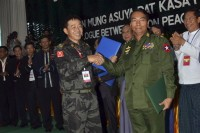 In this file photo, Lt-Gen Myint Soe of Burma's Defense Ministry (r) shakes hands with Maj-Gen Gun Maw of the Kachin Independence Army during peace talks in Myitkyina, Kachin State  in October 2013. (PHOTO: AP)
