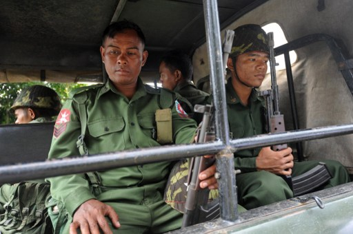 Burmese soldiers sit on an convoy near Thandwe, where communal violence erupted in late September 2013 (AFP)
