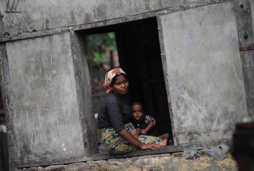 A Rohingya woman holds her child as she looks out from her shelter at a displacement camp in Sittwe, Arakan State. (PHOTO: AFP)
