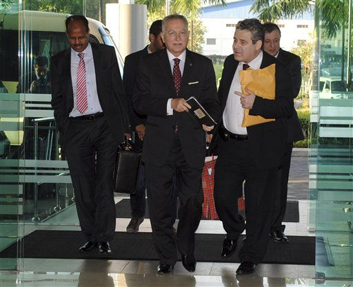 OIC Secretary-General Ekmeleddin Ihsanoglu, center, and other delegates arrive at Rangoon International Airport to leave Burma on Sunday, 17 November 2013. (AP PHOTO)