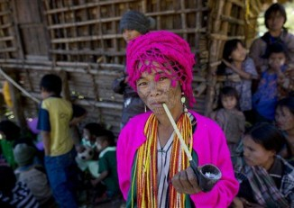 An ethnic Chin woman of the Muun sub-tribe with traditional tattooed face smokes a pipe with tobacco in Kyar Do village. (AP Photo/Gemunu Amarasinghe)